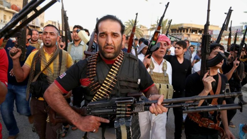 Iraqi Shiite tribal fighters deploy with their weapons while chanting slogans against the Al Qaeda-inspired Islamic State of Iraq and Syria.
