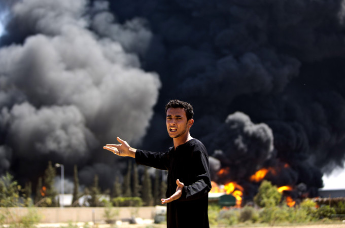 A Palestinian man reacts as flames engulf the fuel tanks of the only power plant supplying electricity to the Gaza Strip after it was hit by overnight Israeli shelling, on July 29, 2014, in the south of Gaza City. The damage of the power plant exacerbated the heavy damage to civilian infrastructure in Gaza already inflicted during the 22 days of the Israeli offensive aimed at stamping out militant rocket fire and destroying attack tunnels. AFP PHOTO/MAHMUD HAMSMAHMUD HAMS/AFP/Getty Images