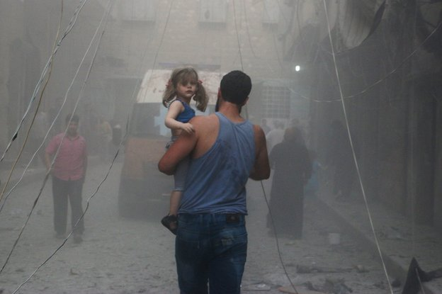 A Syrian man carries a girl on a street covered with dust following a government airstrike in Aleppo on Tuesday. Rebels took the eastern half of the city in 2012 but are now in danger of being forced out by President Bashar Assad's troops. (Baraa Al-Halabi/AFP/Getty Images)