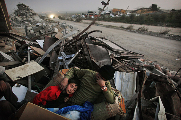 A family rests on the rubble of their home in Jebaliya (Time Magazine)