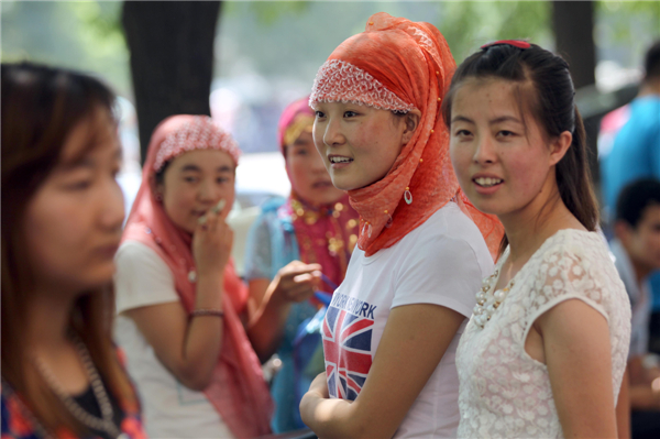Female Muslims smile wearing hijabs as they attend a festival at Niujie Mosque in Beijing on Aug 8, 2013, part of activities to celebrate Eid Al-Fitr marking the end of Islam's fasting month of Ramadan. [Zou Hong/Asianewsphoto]