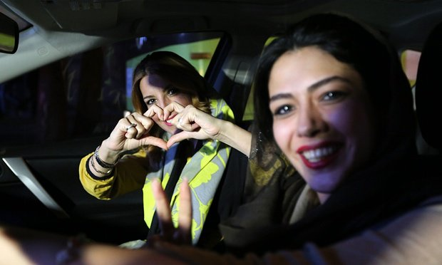 Iranian women flash a heart sign during celebration in northern Tehran on 14 July 2015.